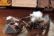 The most sophisticated machines don't necessarily triumph in the violent gladiatorial battles at San Francisco's Robot Wars, as shown when Tazbot (with turret), a simple, remote-controlled vehicle, forces a much more sophisticated, autonomously moving opponent to self-destruct. San Francisco, CA. From the book Robo sapiens: Evolution of a New Species, page 204 bottom.
