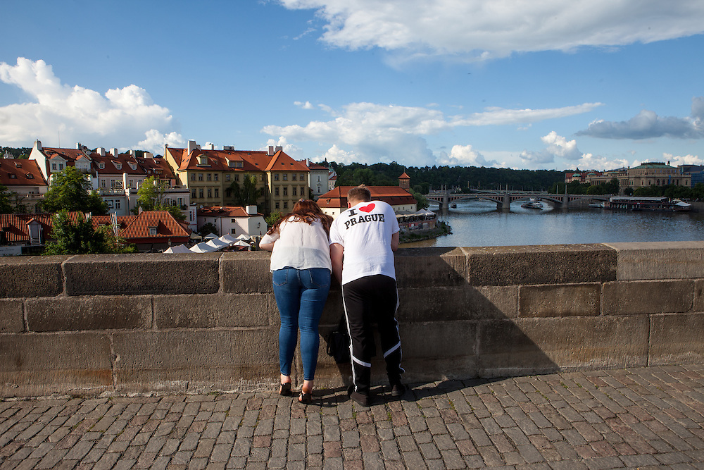 "A visitor wearing a T-Shirt with the writing ""I love Prague"" on Charles Bridge in the Czech capital. The Charles Bridge (Czech: Karlův most) is a famous historic bridge that crosses the Vltava river in Prague, Czech Republic and is probably the Nr.1 tourists magnet in the city."