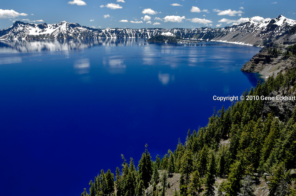 Crater Lake - Crater Lake National Park - Oregon - United States<br /> <br /> About 6,800 years ago, at the climax of a series of dramatic eruptions, the top of Mt. Mazama collapsed.  Left behind was the huge crater, or caldera, you see today.  But before the caldera filed with water, there were more eruptions.<br /> <br /> The most striking evidence of post-collapse volcanic activity is Wizard Island, the small volcano in the middle of Crater Lake.  It's symmetrical cone was formed by a fountain of cinders which erupted from the caldera floor.  On the left side of the caldera, a similar cone appeared, but today it lies hidden 496 feet (151m) beow the lake surface. <br /> <br /> Geologists believe that lava flows which erupted after the collapse helped to seal the fractured caldera floor, allowing melting snow and rain to accumulate. <br /> <br /> When Mt. Mazama collapsed about 6,800 years ago, it left behind evidences of its former self.  Like X-ray photos, the steep caldera walls reveal the interior of Mt. Mazama before its fall.  <br /> <br /> The massive gray monolith on the rim is Llao Rock.  It formed when a large outpouring of lava filled an explosion crater on the north slope of Mt. Mazama.  When Mt. Mazama collapsed, part of the hardened lava flow broke off and fell into the caldera, leaving the downslope portion perched on the rim.<br /> <br /> The jagged, colorful spires of Hillman Peak are the remains of a secondary volcano which erupted on the side of Mt. Mazama.  This satellite cone attained a height of 1,000 feet (300m). Erosion has exposed a maze of clogged and solified lava conduits that fed the Hillman volcano.
