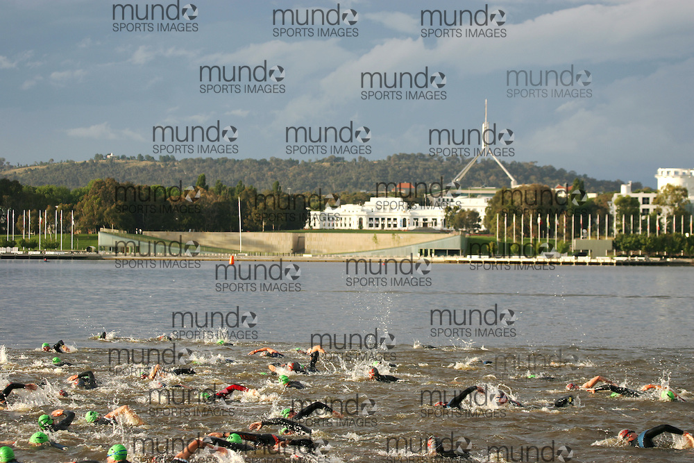 (Canberra, Australia---10 December 2011) Competitors in the 2011 Ironman 70.3 Canberra triathlon leave the deep water start of the swim section in Lake Burley Griffin with Old Parliament House and the current Parliament building visible in the background. Photograph 2011 Copyright Sean Burges / Mundo Sport Images. For usage terms contact info@mundosportimages.com or seanburges@yahoo.com.