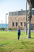 woman Slacklining in Charles Clore park, Tel Aviv-Jaffa with Elinor Cohen. Photography: Ilan Rosen