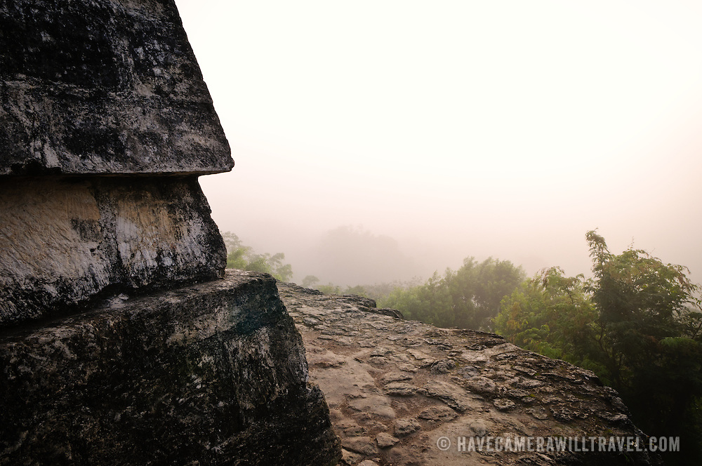 At left is part of the top of Temple IV, the tallest of the pyramids at Tikal. At right of frame, the rising sun illuminates the mists over the jungle canopy.