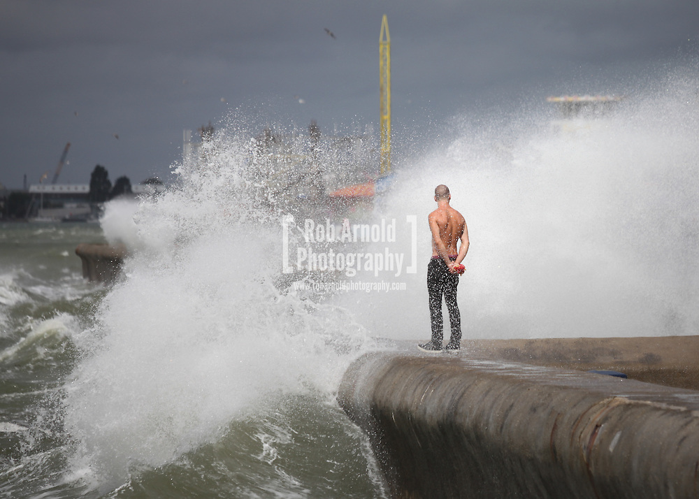 A man standing on the seawall in Southsea, Hampshire during Hurricane Bertha, which hit the UK in August 2014