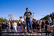 28 JULY 2020 - DES MOINES, IOWA: A member of Black Lives Matter stands on a railing along Grand Ave during a march to the Governor's Mansion in Des Moines. About 150 supporters of Black Lives Matter marched from downtown to Des Moines to the Governor's Mansion. They were demanding that Iowa Governor Kim Reynolds restore the voting rights for felons who have completed their sentence. In June, Reynolds met with representatives of Black Lives Matter and promised to sign an executive order to restore voting rights, but she hasn't said anything more about it in six weeks. Iowa is now the only state in the US that permanently strips felons of their voting rights. That means 60,000 people in Iowa can't vote.    PHOTO BY JACK KURTZ