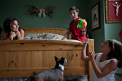 "Vanessa Gonzalez is seen with her children, Santiago and Andrea, as they play with their dog Leo in Littleton, Colo., Aug. 29, 2011. Santiago, 13, is a full-time college student at the Colorado School of Mines, an engineering university. He wakes up at 5:30 a.m. every morning during the academic semester to develop iPad and iPhone applications in a programming language called Objective C, which he learned from a textbook when he was 9 years old. That textbook and 86 similar volumes including Applied Finite Mathematics, Infinity in Your Pocket, Programming in C++ and Dictionary of Physics, sit in a glass-fronted bookcase opposite his bed. ""Exceptionally gifted"" is the commonly used phrase for kids as smart as Gonzalez."