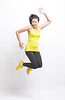 Portrait of young Asian woman in yellow tank top and leggings jumping against white background