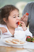 Cute little girl eating strawberry with father at breakfast table