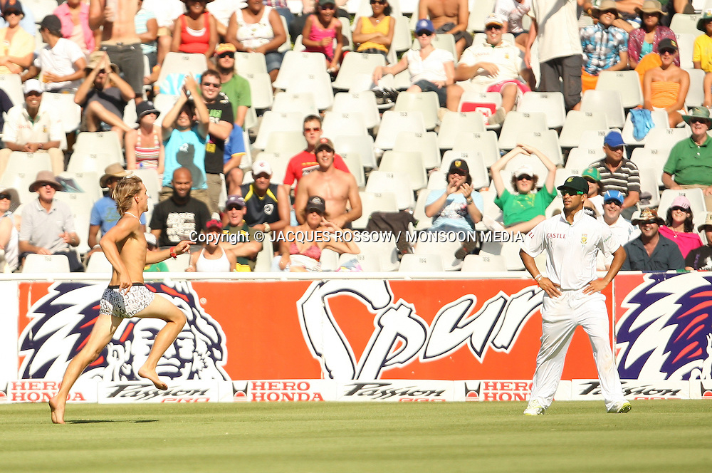 A spectator runs across the field with JP Duminy looking on during Day 2 of the third and final Test between South Africa and India played at Sahara Park Newlands in Cape Town, South Africa, on 2 January 2011. Photo by Jacques Rossouw / MONSOON MEDIA