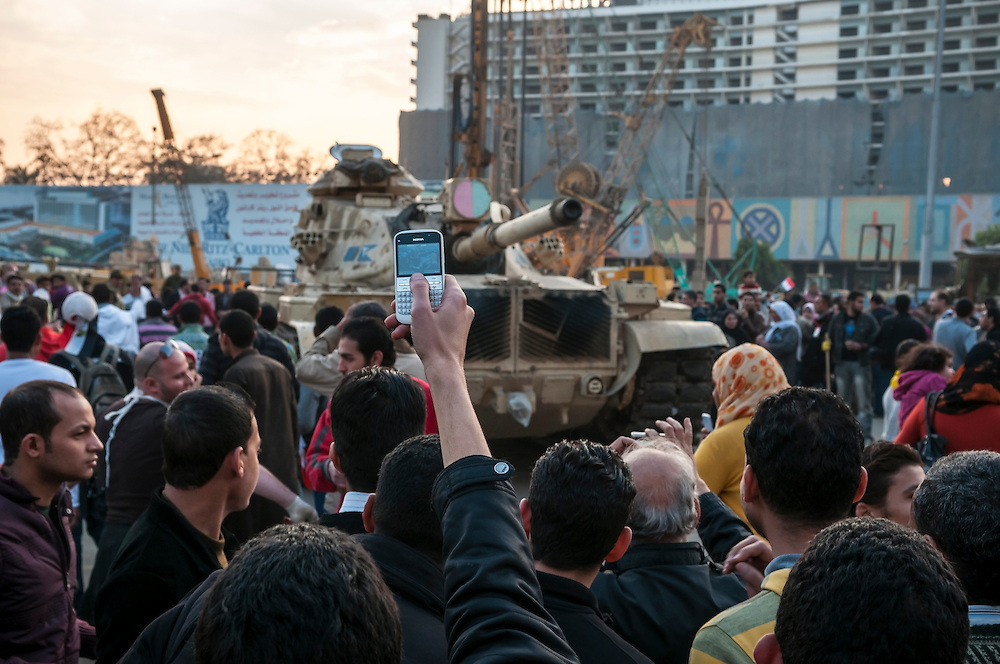 The day after 18 days of demonstrations led to the resignation of Egyptian President Hosni Mubarak, crowds gather again in Tahrir Square in celebration, some taking photos with their smartphone of a tank. (Cairo, Egypt - February 12, 2011)