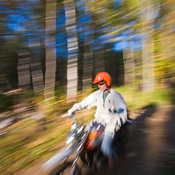A man rides his motorcycle through the forest at Jericho Mountain State Park in Berlin, New Hampshire.  White Mountains.