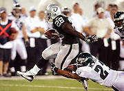 CANTON, OH - AUGUST 6:  Running back DeJaun Green #28 of the Oakland Raiders tries to escape a shoestring tackle by cornerback Matt Ware #21 of the Philadelphia Eagles during the AFC-NFC Pro Football Hall of Fame Game at Fawcett Stadium on August 6, 2006 in Canton, Ohio. The Raiders defeated the Eagles 16-10. ©Paul Anthony Spinelli *** Local Caption *** DeJaun Green;Matt Ware