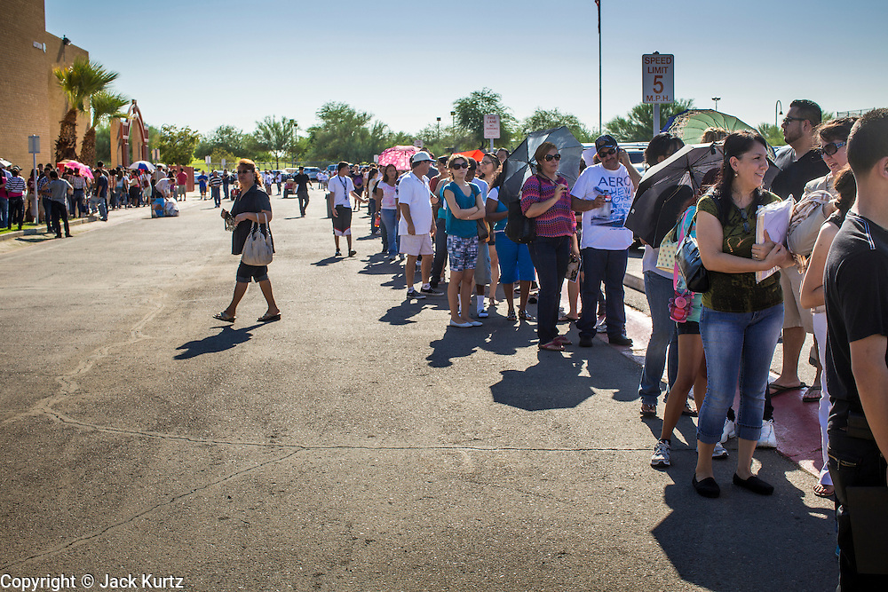 """25 AUGUST 2012 - PHOENIX, AZ:  People wait in the parking lot for the deferred action workshop to open its doors Saturday morning. The line snaked through the parking lot. Hundreds of people lined up at Central High School in Phoenix to complete their paperwork to apply for """"Deferred Action"""" status under the Deferred Action for Childhood Arrivals (DACA) program announced by President Obama in June. Volunteers and lawyers specialized in immigration law helped the immigrants complete the required paperwork. Under the program, the children of undocumented immigrants brought to the US before they turned 16 years old would not be subject to deportation if they meet a predetermined set of conditions.    PHOTO BY JACK KURTZ"""