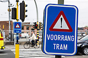 "Blue road warning sign ""Voorrang Tram"" at a pedestrian street crossing in Ghent, Belgium.  A cyclist on a bike and car traffic travel past in the background."