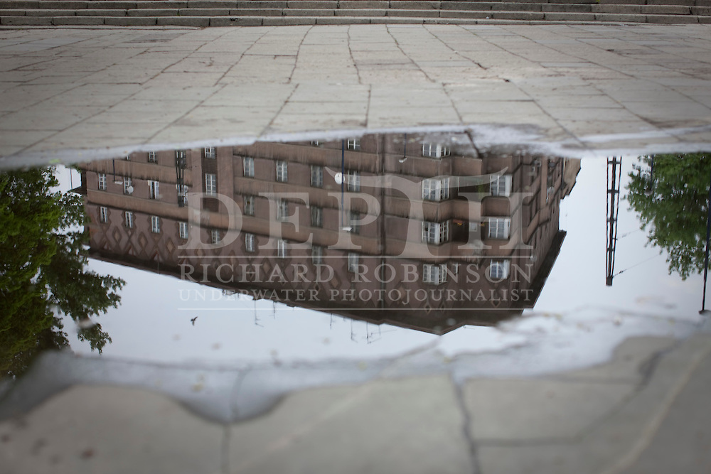 Buildings reflected in a puddle on a grey day in Krakow, Poland..Tuesday 04 May 2010.Photograph Richard Robinson © 2010.