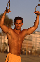 shirtless All American man holding workout rings in Santa Monica, CA