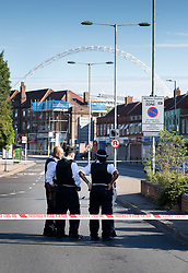 © Licensed to London News Pictures. 06/07/2019. London, UK. Police gather on the Harrow Road near Wembley Stadium after a man was shot on Friday night. The victim, believed to be a man in his 30s, was found with fatal gun shot wounds at 8pm near a mosque. No arrests have so far been made. Photo credit: Peter Macdiarmid/LNP