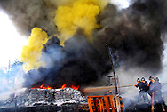Fire brigade officials extinguish a fire in a chemical container in a container yard in Mumbai October 22, 2006.