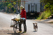 A woman is using a bicycle as she sells street food on a city street in Kampong Cham, Cambodia.