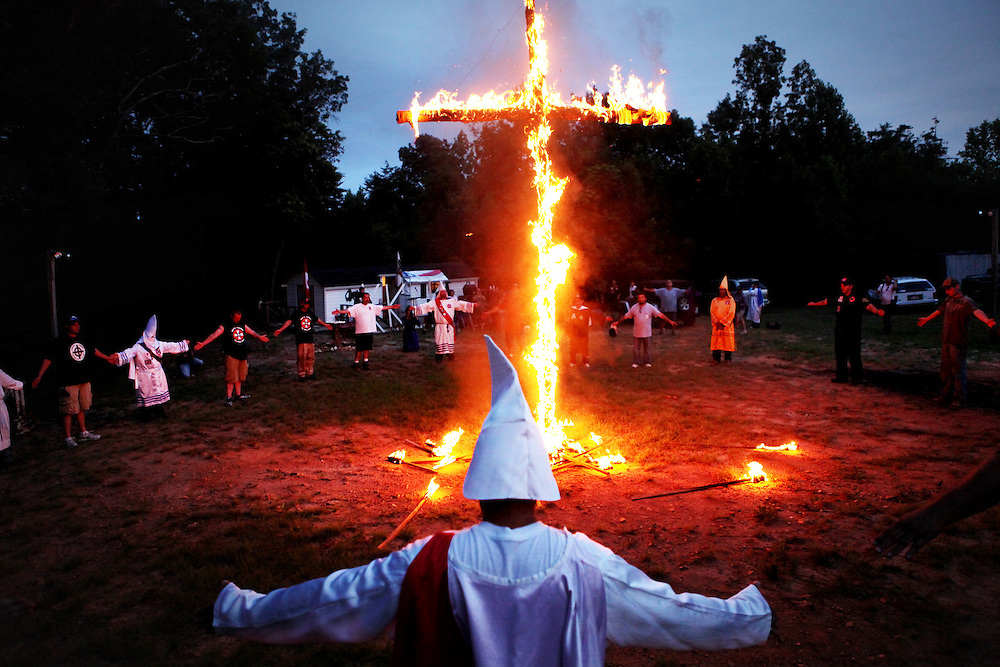 Kyle Green | The Roanoke Times<br /> 7/2/2011 Members of the Rebel Brigade KKK group in Martinsville, Virginia stand hand in hand as a large cross burns one of six cross burnings held on rural land in southwest Virginia. The KKK is making a comeback in the USA helped by high unemployment and a growing distrust in the government.