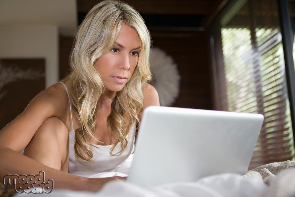 Woman sits working on laptop in home interior