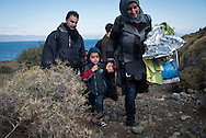 In this photo a refugee family walks up from the beach. The coastline in the distance, around six miles away and from which they had just come, is Turkey. This photo was taken on Sunday morning. In the week ahead, scores would lose their lives attempting this same journey.<br />