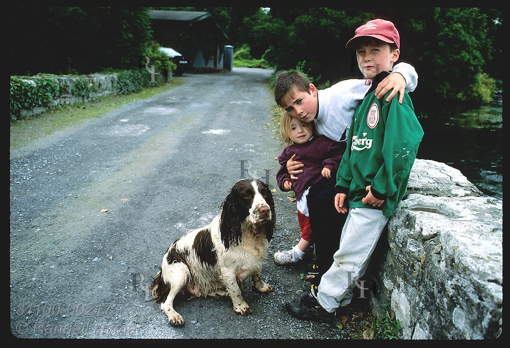 Two boys and a girl pose with their dog for picture in village of Cong. Ireland