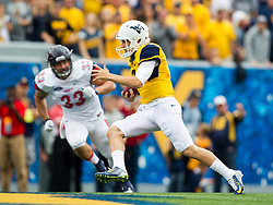 Sep 12, 2015; Morgantown, WV, USA; West Virginia Mountaineers quarterback Skyler Howard runs the ball up the middle against the Liberty Flames during the first quarter at Milan Puskar Stadium.  Mandatory Credit: Ben Queen-USA TODAY Sports