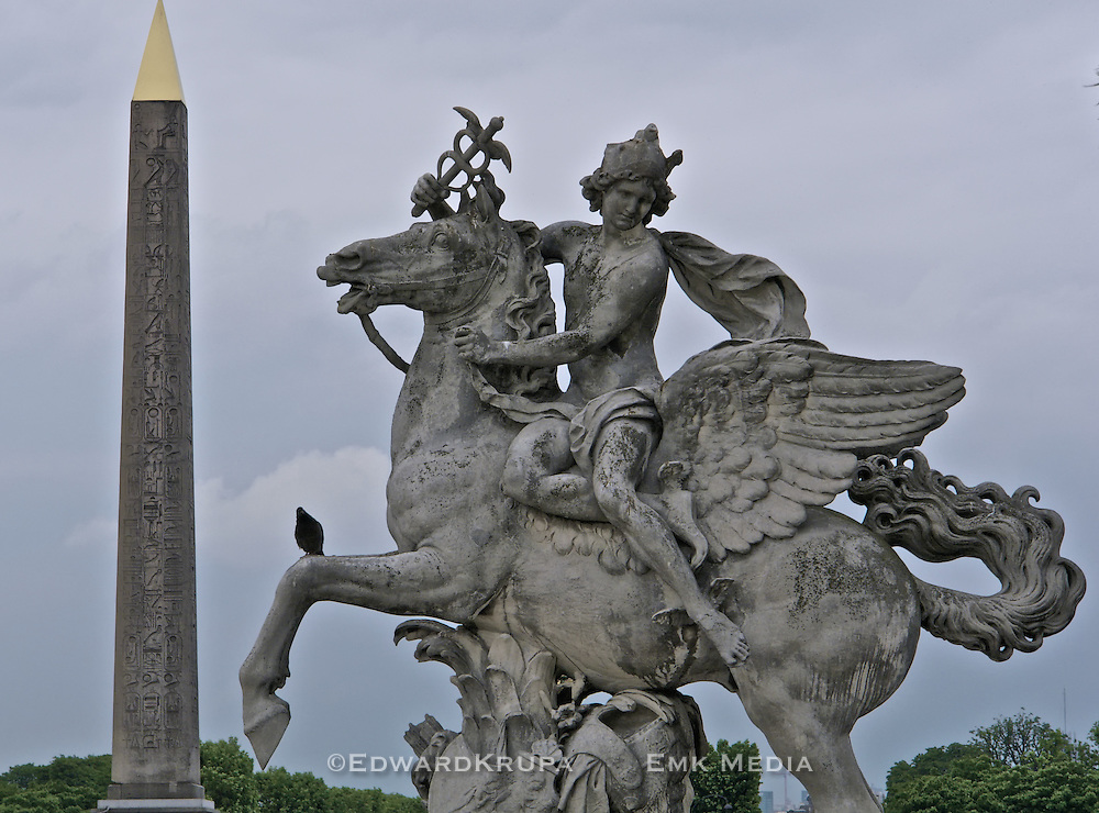 Pigeon sits on Man on Winged Horse statue with Cleopatras needle in background, Paris.