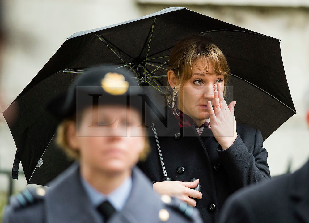 © Licensed to London News Pictures. 04/11/2015. London, UK. An emotional woman wipes a tear from her eye during the service. Service to mark the opening of the Filed of Remembrance at Westminster Abbey, attended by Prince Philip, Duke of Edinburgh and Prince Harry.  The Field of remembrance is a memorial garden to commemorate British and Commonwealth military and civilian servicemen and women in the two World Wars and later conflicts. Photo credit: Ben Cawthra/LNP