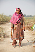 A freed woman stands in her new village of Azadnagar which means 'Village of the Freed'. Following the release of the Global Slavery Index by the Walk Free Foundation Pakistan is ranked 3rd worse in the world behind India and China. The Asian Development Bank estimates some 1.8 million people are slaves in Pakistan yet other estimates reach up to 4 million people, most of which toil year after year in brick kilns or sugar cane plantations. Their stories are the same; they have no-where to turn so they borrow money from a land-owner for a medical emergency or marriage dowry. The landlords pay in return for work, their labour supposed to be taken off the amount borrowed. Yet after years of no salary incredibly their amount owed is often quadrupled, the excuse being the amount they cost to feed! Many are chained, abused, raped and even killed.<br /> <br /> For years they had no where to run, no one to help but now a small local NGO called the Green Development Rural Organisation (GDRO) works to free bonded-slaves by using the law against their captives. Yet, often freed slaves end up right back where they were or risk being hunted by the landowner and forced to return. So GRDO started building villages so slaves who escape or are freed have somewhere safe to go. It now has two, whose names translate from Urdu as 'Village of the Freed' and 'Village of the Courageous', and is working on a 3rd. The land is bought and allocated to freed slave families where they can built a house and start again. Without such help the vicious cycle would continue.