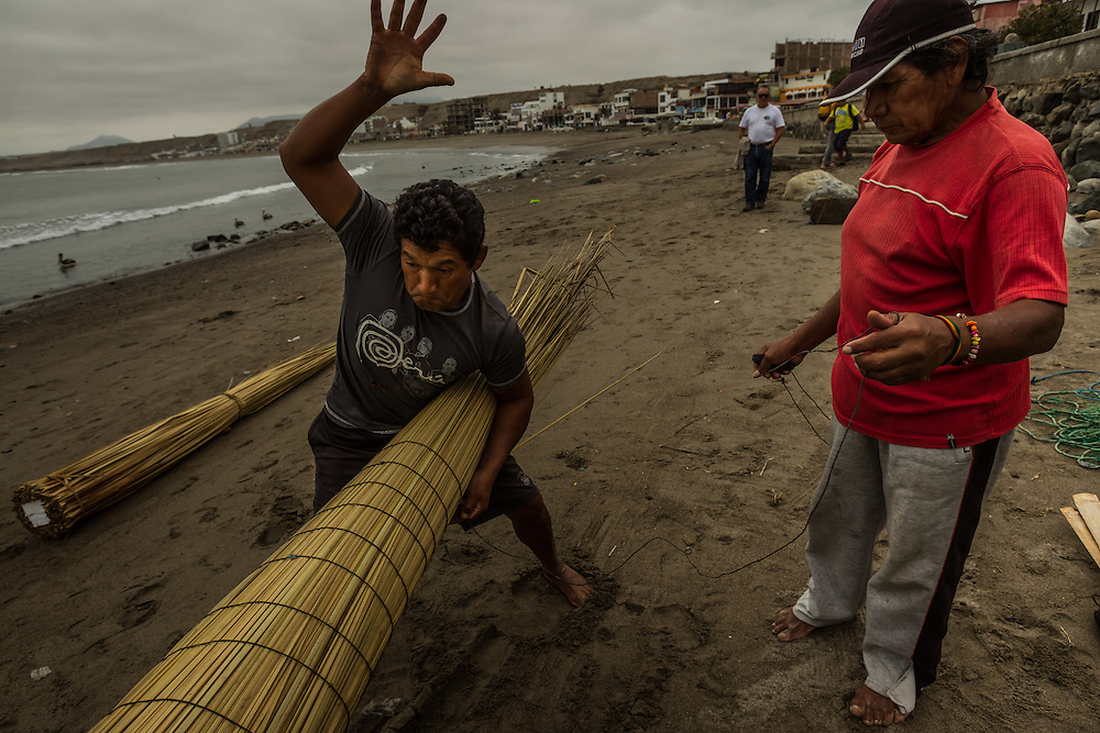HUANCHACO, PERU - JULY 14, 2014: Carlos Ucañan Arzola, 41, (left) smacks reeds into place while building a reed boat with pointy, upswept prows known as caballitos de totora, or little totora reed horses. Centuries before the Spanish arrived and long before the Incas extended their empire from the mountaintops to the coast, fishermen here were building boats from the totora reed that grows along the shore. Today a handful of fishermen keep up that tradition, growing and harvesting the reeds and forming them into the boats that have been used by fishermen for thousands of years in Huanchaco. PHOTO: Meridith Kohut for The New York Times