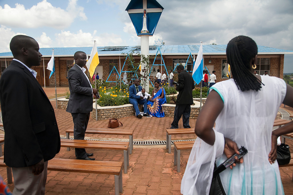 A family gets photographed under a Virgin Mary statue at the Shrine of Our Lady of Sorrows in Kibeho, Rwanda. This is the only sanctioned Marian sanctuary in Africa. Kibeho's overseers and the Rwandan government hope this place will become a top tourism site. This statue marks one of the spots where three young Rwandan women had visions of Mary. The very first vision came to Alphonsine Mumureke, then 16, on Nov. 28, 1981.<br /> <br /> Photographed on Sunday, October 26, 2014.<br /> <br /> Photo by Laura Elizabeth Pohl