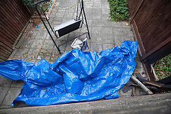 NOTE TO EDITORS : IMAGE TAKEN FROM A SUPERMARKET CAR PARK © Licensed to London News Pictures. 19/07/2019. London, UK. Plastic sheeting covers an area next to burnt timbers (R) in the back garden of a house where it is reported that the body of a woman was found on fire in Chadwell Heath, East London. Fire fighters arrived at the house and then called in the police when they found the woman. Photo credit: Peter Macdiarmid/LNP