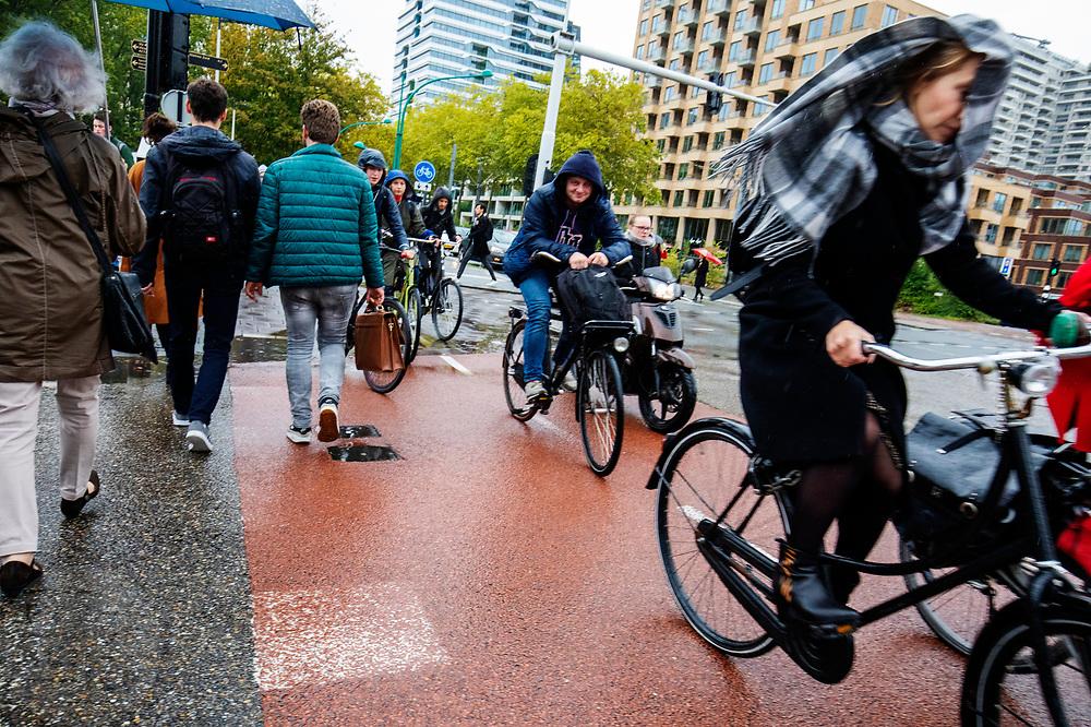In Amsterdam-Zuid rijden fietsers door de regen. Bij een vrouw waait de sjaal voor haar gezicht.<br /> <br /> In Amsterdam cyclists ride in the rain.