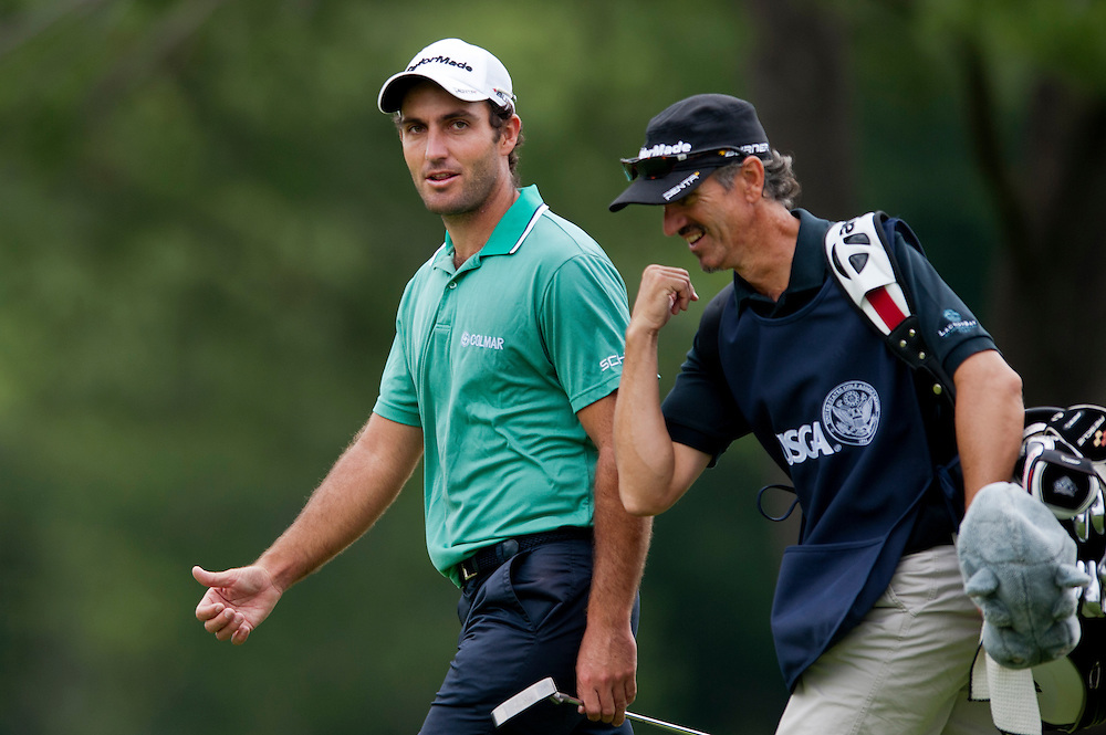 EDOARDO MOLINARI talks with his caddie as they walk down the 4th fairway at Congressional Country Club during the first round of the U.S. Open in Bethesda, MD.