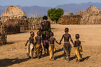 Arbore tribe girls walking and holding hands, Omo Valley, Ethiopia.