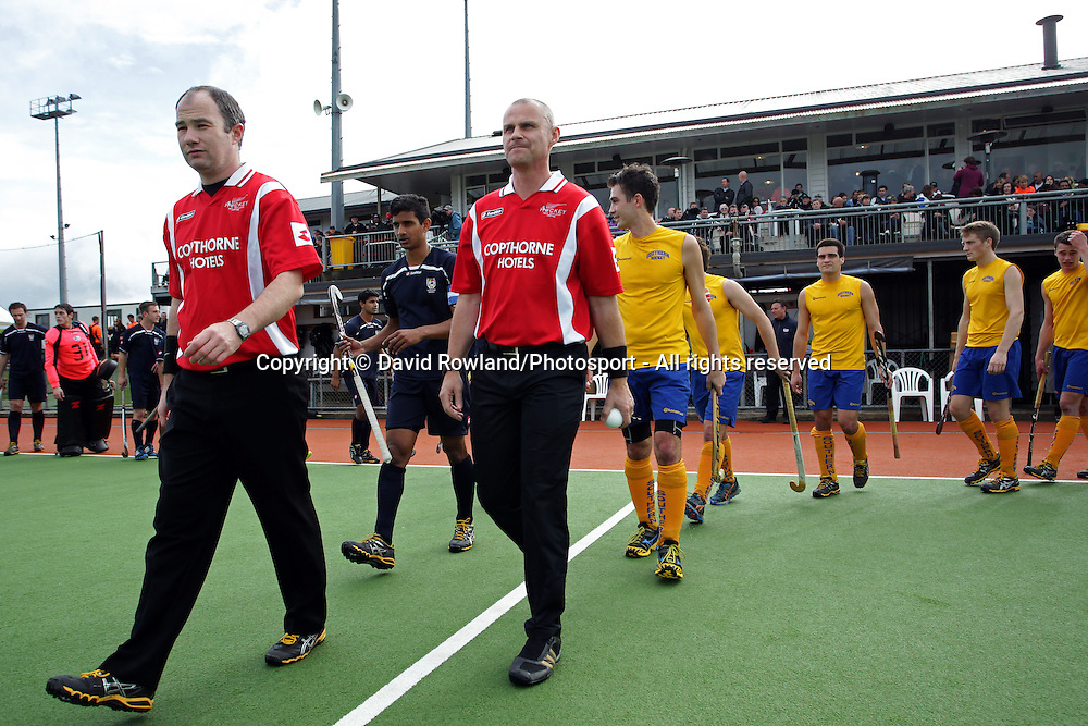 Umpires Gareth Greenfield and Simon Taylor lead Auckland and Southern on to the field for the Ford National Hockey League Final, North Harbour Hockey Stadium, Auckland, New Zealand, Sunday, August 25, 2013. Photo: David Rowland/Photosport