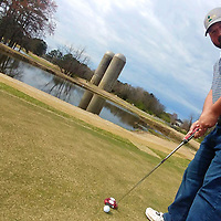 Andy Willingham prepares to putt with River Birch Golf Club's signature silos pictured in the background. He and his wife, Kathy, purchased the course and changed its name back from Ackia Golf Course.