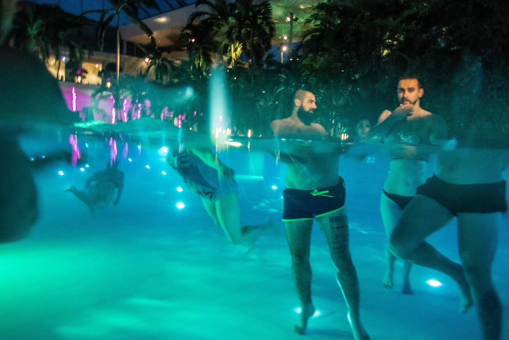 People are enjoying a large swimming pool in a big thermal spa complex north of Bucharest.