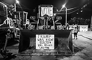 Two signs, one suggesting a rigged election and another demanding people to vote in 2020 are place on an excavator parked in a construction site next to an anti-trump protest in West Palm Beach on February 4, 2017. (photo by Samuel Navarro)