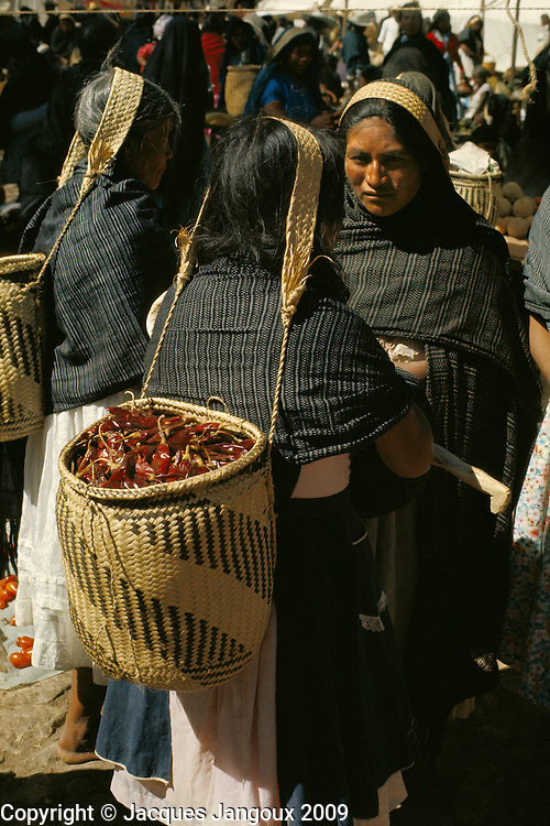 Indian women at market in village in Oaxaca State, Mexico; baskets are carried using tumpline.