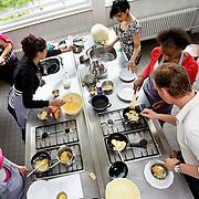 Nederland Rotterdam 4 juni 2008 20080604 Foto: David Rozing .VMBO leeringen van brede school Nieuw Zuid aan de Putsebocht in Rotterdam zuid krijgen kookles .De brede school is - in Nederland - een definitie voor de samenwerkende partijen die zich bezighouden met opgroeiende kinderen. Hierbij hoort in ieder geval onderwijs en welzijn, maar vaak ook kinderopvang, cultuur, sport, de bibliotheek, enz. In de praktijk is de brede school een plaats waar school en voor- en naschoolse opvang in elkaar samenvloeien..De brede school is een samenwerkingsverband tussen partijen die zich bezighouden met opgroeiende kinderen. Doel van het samenwerkingsverband is de ontwikkelingskansen van de kinderen te vergroten. Een ander doel kan zijn een doorlopende, en op elkaar aansluitende opvang te bieden. .De Brede School is geen nieuw begrip meer in Rotterdam. Sinds een aantal jaar breidt een groot aantal onderwijsinstellingen in het primair- en voortgezet onderwijs in Rotterdam het lesprogramma meer en meer uit met een keur aan activiteiten. Dit kunnen activiteiten zijn die zich richten op sociaal-emotionele, fysieke en cognitieve ontwikkeling van leerlingen, maar ook buiten- of voorschoolse activiteiten die de integratie en participatie van leerlingen en ouders bevorderen..Scholen werken samen met verschillende partners (organisaties, verenigingen, etc.) uit de buurt. Op deze manier sluiten binnen- en buitenschoolse activiteiten zo veel mogelijk op elkaar aan. Het doel? Om leerachterstanden te voorkomen en op te heffen, leer- en ontwikkelingsmogelijkheden te vergroten en de leerprestaties van leerlingen te verbeteren. En belangrijk: dat leerlingen kunnen ervaren waar ze aanleg voor hebben en hun talenten verder ontwikkelen. alle Brede Scholen in het Primair Onderwijs in Rotterdam per 1 januari 2007 verplicht voor-, tussen- en naschoolse opvang moeten aanbieden tussen 07.30 uur en 18.30 uur. Dit kan weer belangrijke gevolgen hebben voor het ontwikkelen van dagarrangementen. Daar wil Rot