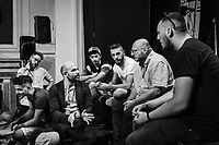 """NAPLES, ITALY - 30 JULY 2018: Roberto Saviano (center), an Italian journalist, writer and essayist is seen here with the young actors and organisers of the collective """"Nuovo Teatro Sanità"""" (New Sanità Theatre) in the Sanità neighborhood, in Naples, Italy, on July 30th 2018.<br /> <br /> In 2017 the 17-year-old innocent victim Genny Cesarano was shot and killed by stray bullet  in cross fire between 2 rival gangs vying for territorial control in the Sanità neighborhood.<br /> The  isolation of the neighborhood Sanità over the years provided an ideal location for the Camorra to expand their illicit activities and profit from soaring unemployment rates and economic instability,<br /> <br /> After the first death threats of 2006 by the Casalese clan , a cartel of the Camorra, which he denounced in his exposé and in the piazza of Casal di Principe during a demonstration in defense of legality, Roberto Saviano was put under a strict security protocol. Since 2006 Roberto Saviano has lived under police protection.<br /> <br /> Saviano's latest novel """"The Piranhas"""", which tells the story of the rise of  a paranza (or Children's gang) and it leader Nicolas, will be released in the United States on September 4th 2018."""