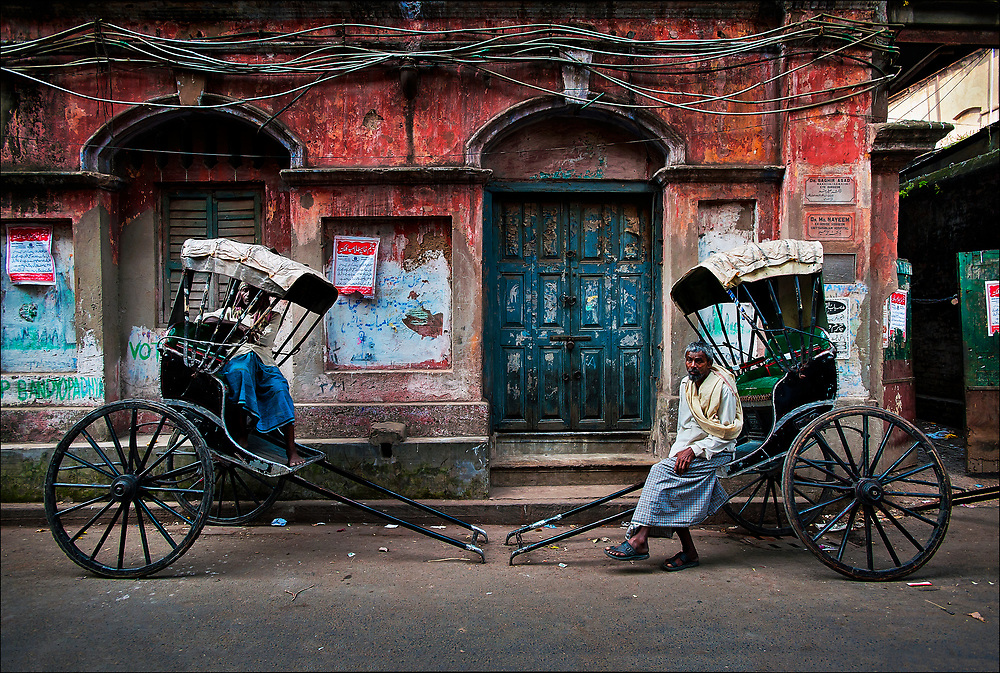 "Like a scene from the early twentieth century, rickshaw-pullers rest on a backstreet in Calcutta, now renamed Kolkata, in West Bengal State. The city's some 6,000 licensed rickshaw drivers are often called ""human horses"" and generally earn less than $5 a day navigating the city's crowded and sometimes flooded streets. © Steve Raymer / National Geographic Creative"