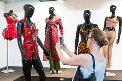 © Licensed to London News Pictures. 26/07/2018. London, UK.  A visitor photographs various clothing and shoes costumes on display at the Spice Girls exhibition. The interactive exhibition features hundreds of iconic stage, music video and film costumes worn by the popular 90s girl band at Business Design Centre/Photo credit: Ray Tang/LNP
