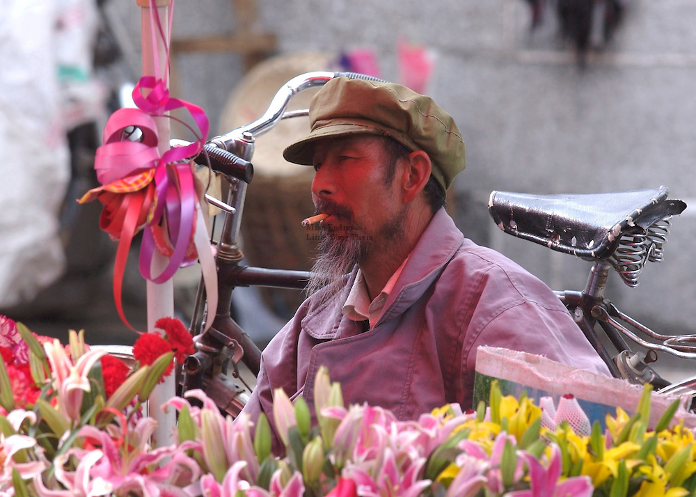 Pink reflections of tulips along with camellia, azaleas, orchids, magnolias and a variety of other flowers reflects on this vendors face below an umbrella. Growing flowers is 'especially popular in the region around Erhai Hu.