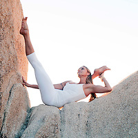Professional yoga teacher high on a rock in a beautiful natural landscape.