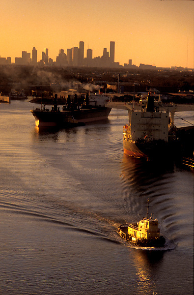 Aerial sunset view of a tugboat and tankers in the Port of Houston with the Houston skyline