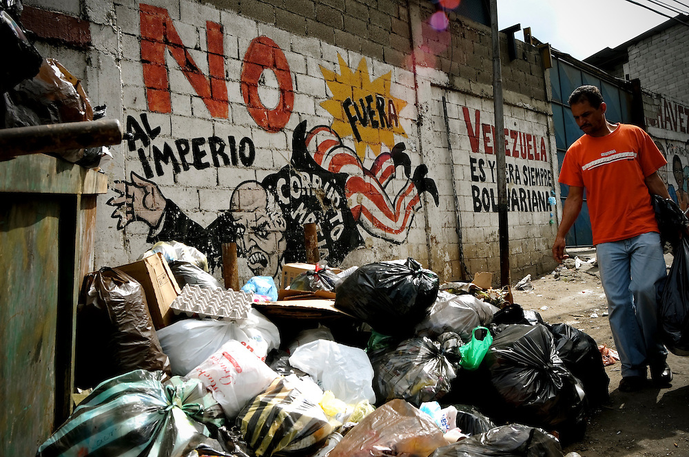 A resident of the El Junquito slum dumps his trash near an overflowing garbage dumpster. People living in Venezuelan slums are faced daily with inadequate municipal services, including water and electricity shortages, poor roads and an unreliable waste management system.