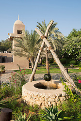 Water well and mosque at Heritage Village tourist attraction in Abu Dhabi United Arab Emirates